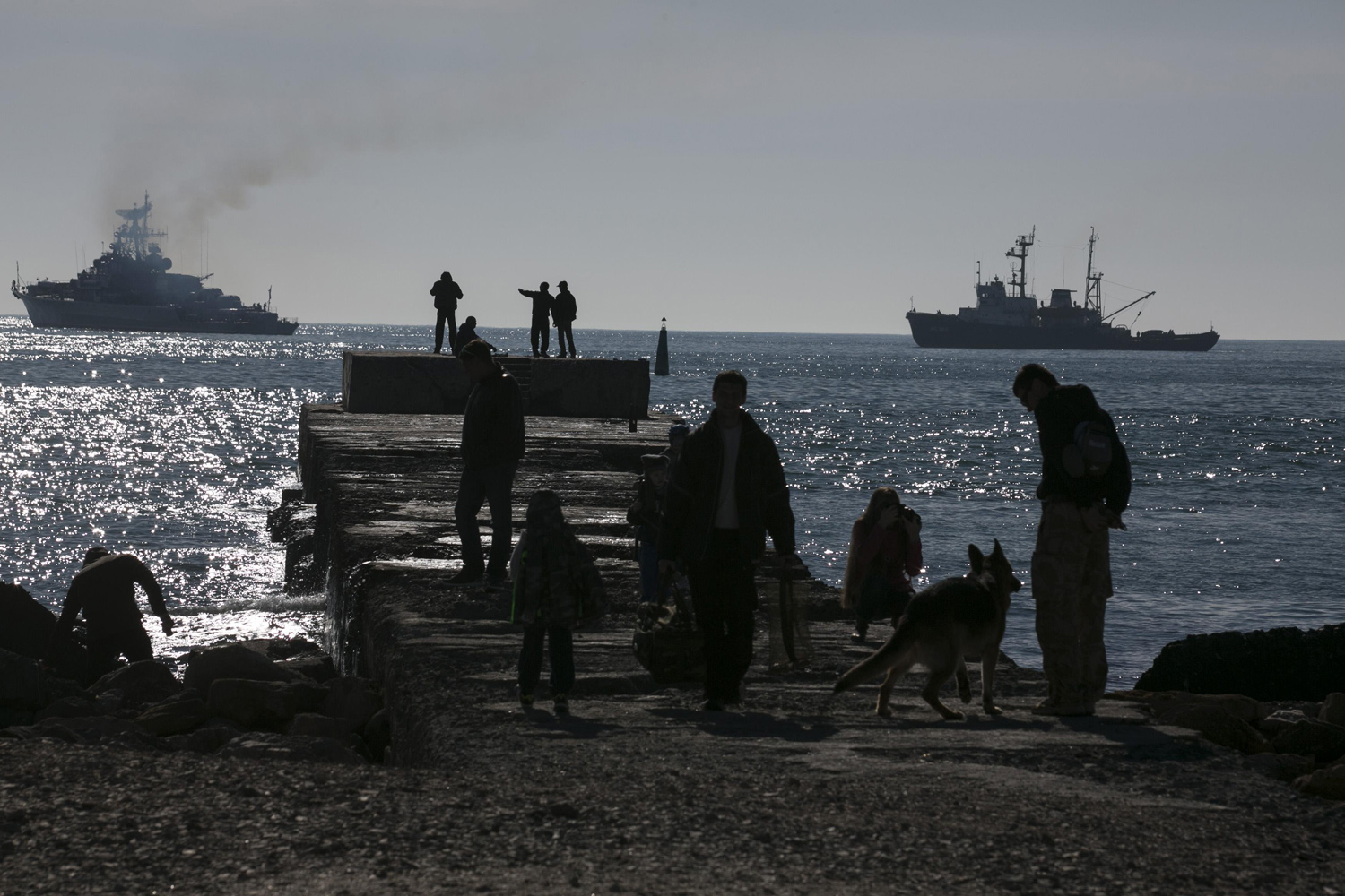 Mar. 23, 2014. People watch Russian ships blockading the exit of Donuzlav bay in Crimea, where three Ukrainian navy ships refused to surrender to Russian forces.