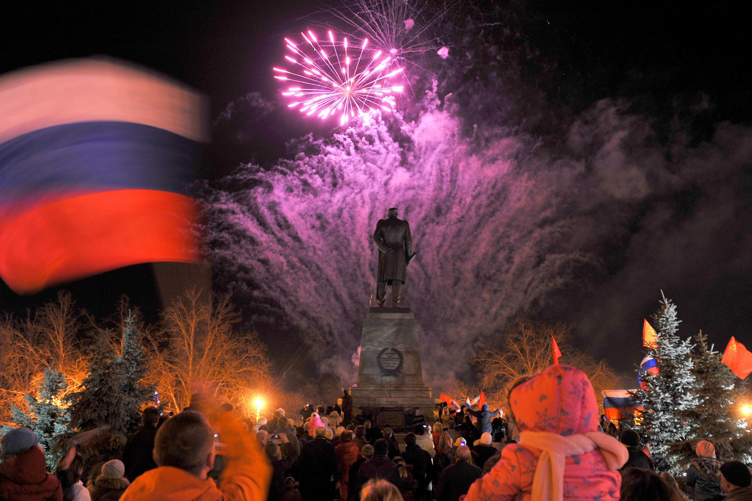 Mar. 21, 2014.  A man waves a Russian flag as people look at fire works in the center of the Crimean city of Sevastopol. Russia's upper house of parliament unanimously voted on March 21 to ratify the treaty incorporating Crimea into Russian territory.