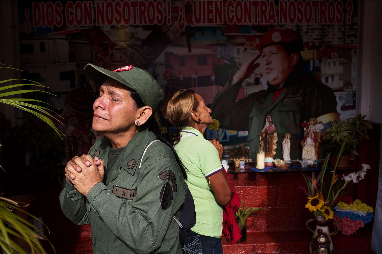 Marisol Perez, Venezuelan Army specialist, cries while visiting a chapel near Venezuela's late President Hugo Chavez's mausoleum in Caracas, March 5, 2014.