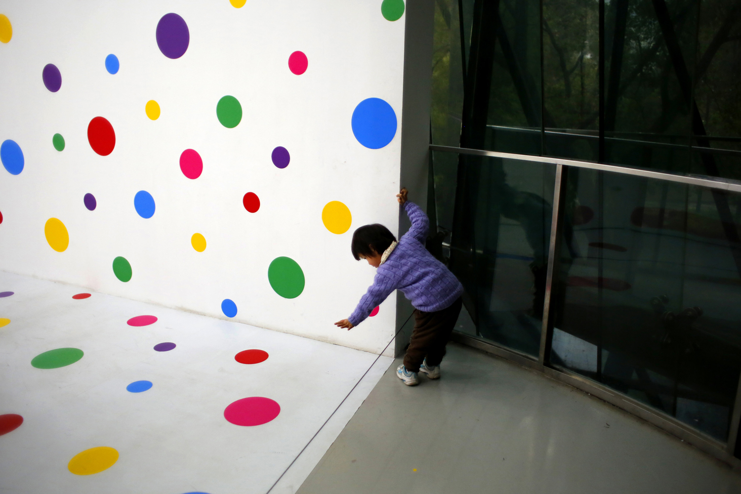 Mar. 25, 2014. A child tries to touch part of the art exhibition 'A Dream I Dreamed' by Japanese artist Yayoi Kusama at the Museum of Contemporary Art of Shanghai.