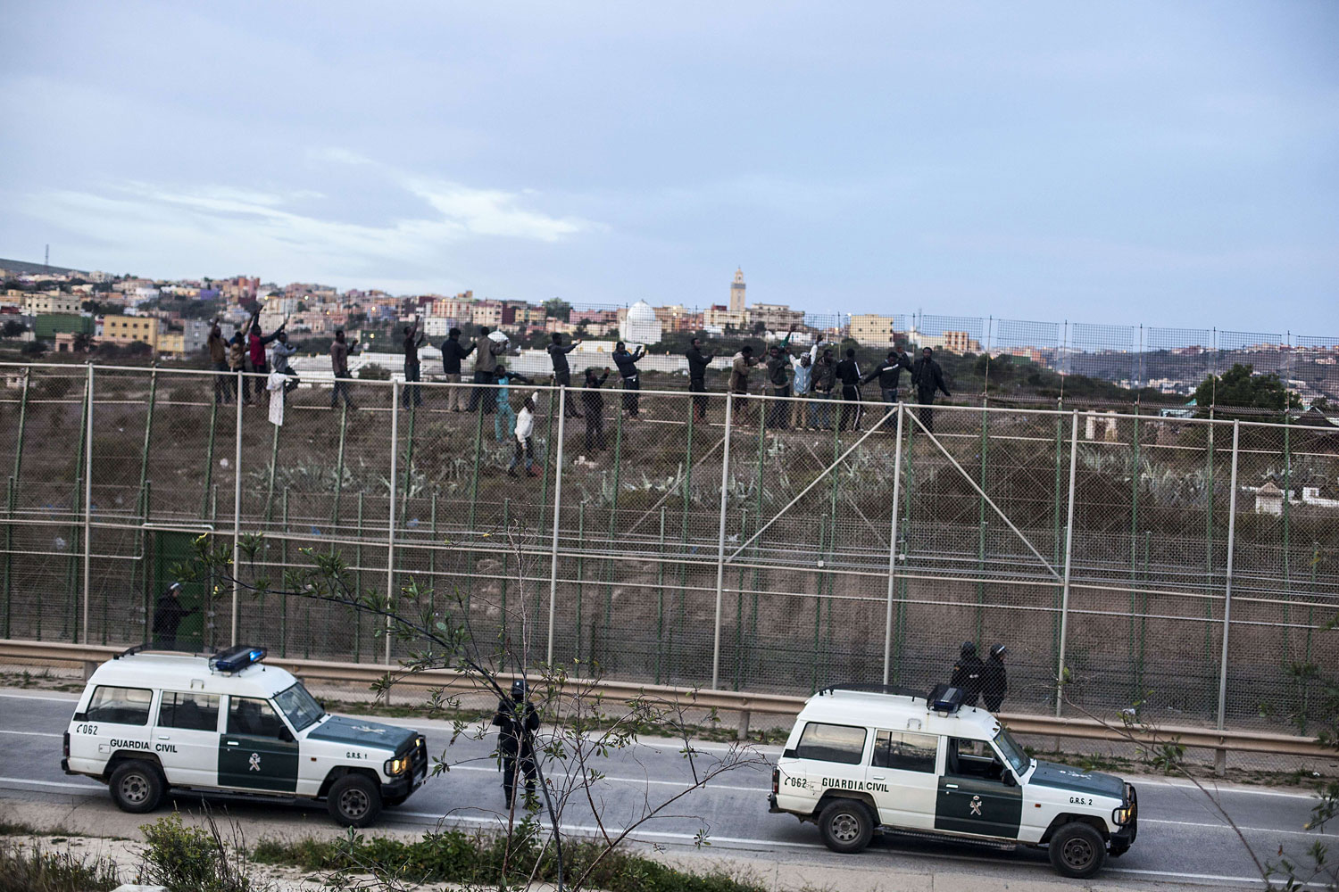 Spanish policemen watch would-be immigrants reacting between two fences near Beni Enza, into the north African Spanish enclave of Melilla on March 28, 2014.