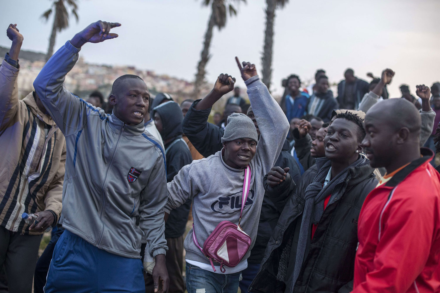 Would-be immigrants of the Centre for Temporary Stay of Immigrants cheer others who want to cross the fence near Beni Enza, into the north African Spanish enclave of Melilla on March 28, 2014. Hundreds launched a dawn assault to cross into the Spanish city and dozen made it across.