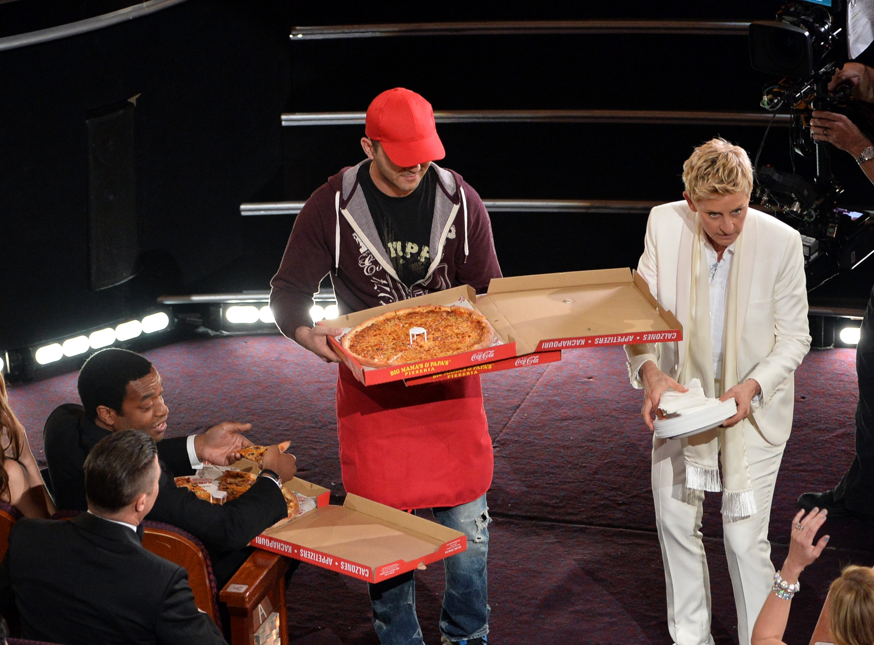 Host Ellen DeGeneres (right) and actor Chiwetel Ejiofor (far left) with pizza delivery man in the audience during the Oscars at the Dolby Theatre on March 2, 2014 in Hollywood.