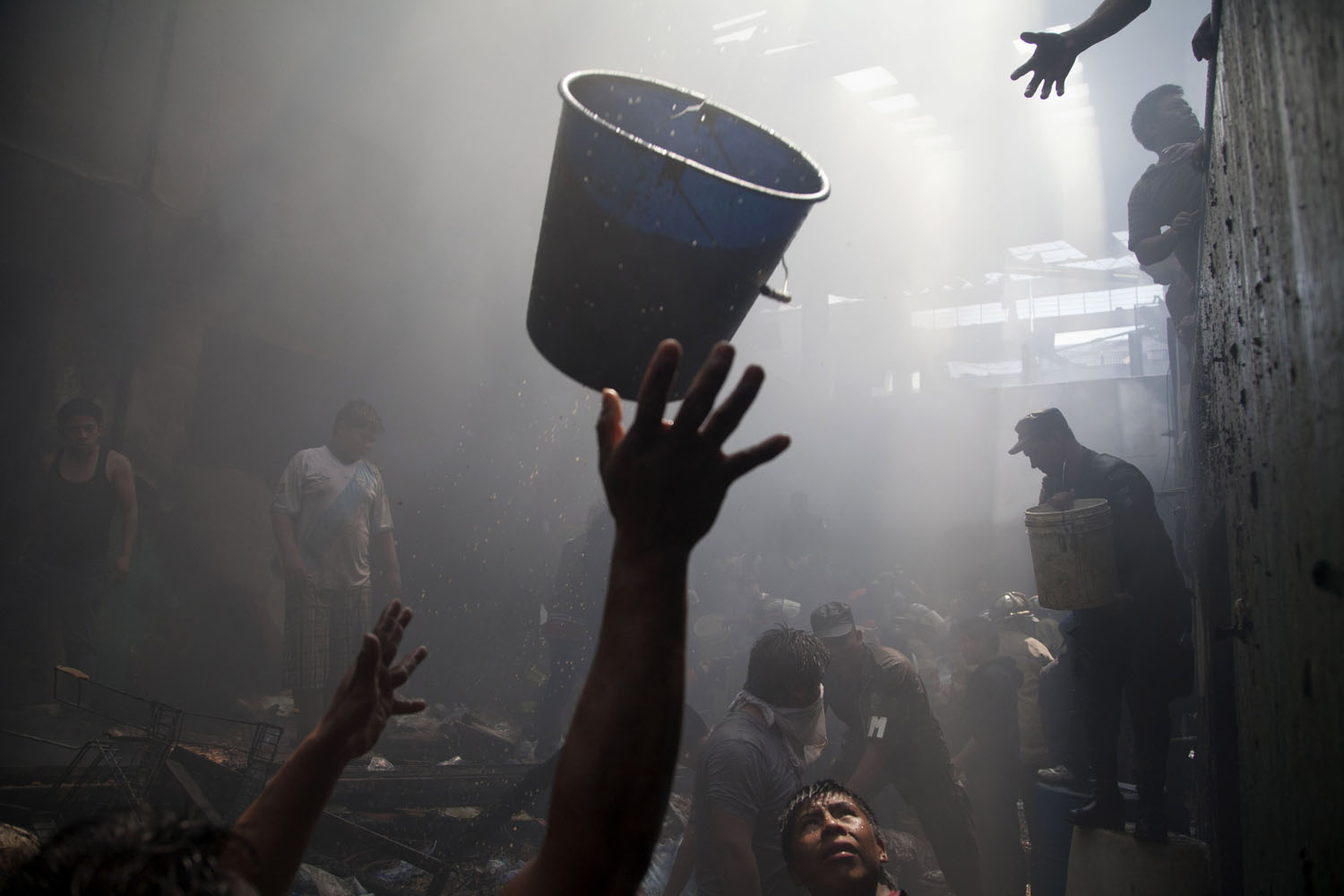 Mar. 25, 2014. Hands reach out to receive a bucketful of water as vendors, police and firemen work together to put out a fire at La Terminal, the largest and most important market in Guatemala City.