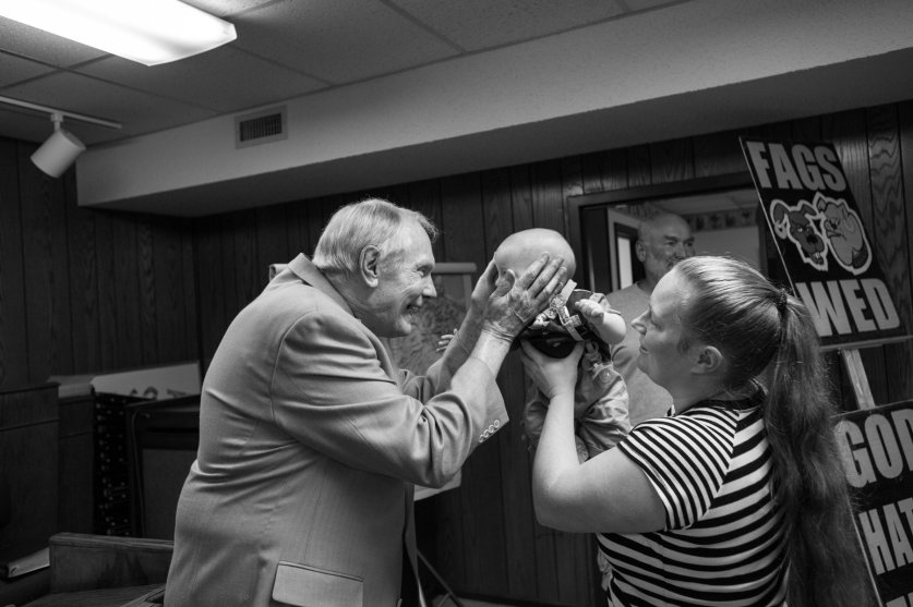 Pastor Fred Phelps greets one of his many grandchildren immediately following a one-hour-long Sunday service.