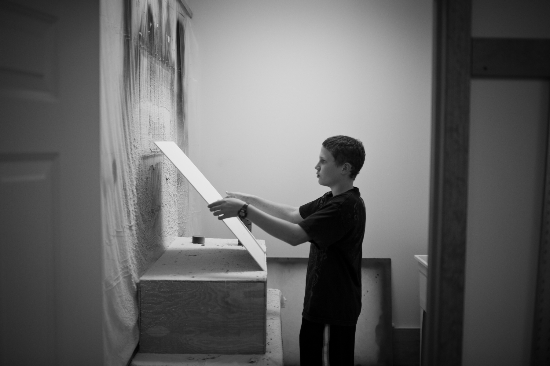 """Jonah Phelps-Roper prepares a picket sign in the """"spray room."""" The room is part of the sign shop, which is a highly efficient production facility within the Westboro compound."""