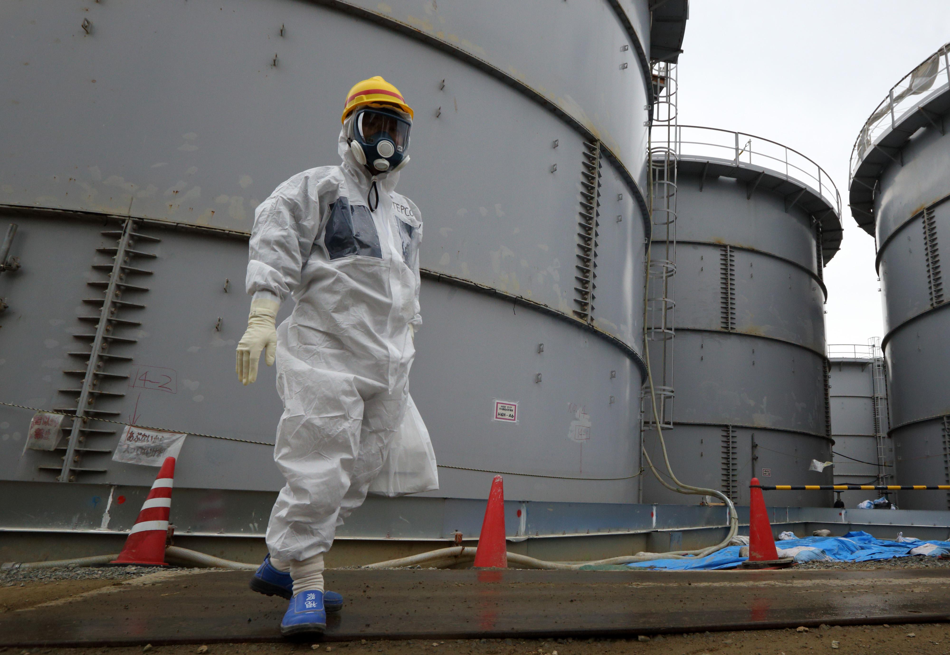 A Japanese power company employee walks past storage tanks for radioactive water at the Fukushima Daiichi plant Japan, in Nov., 2013.