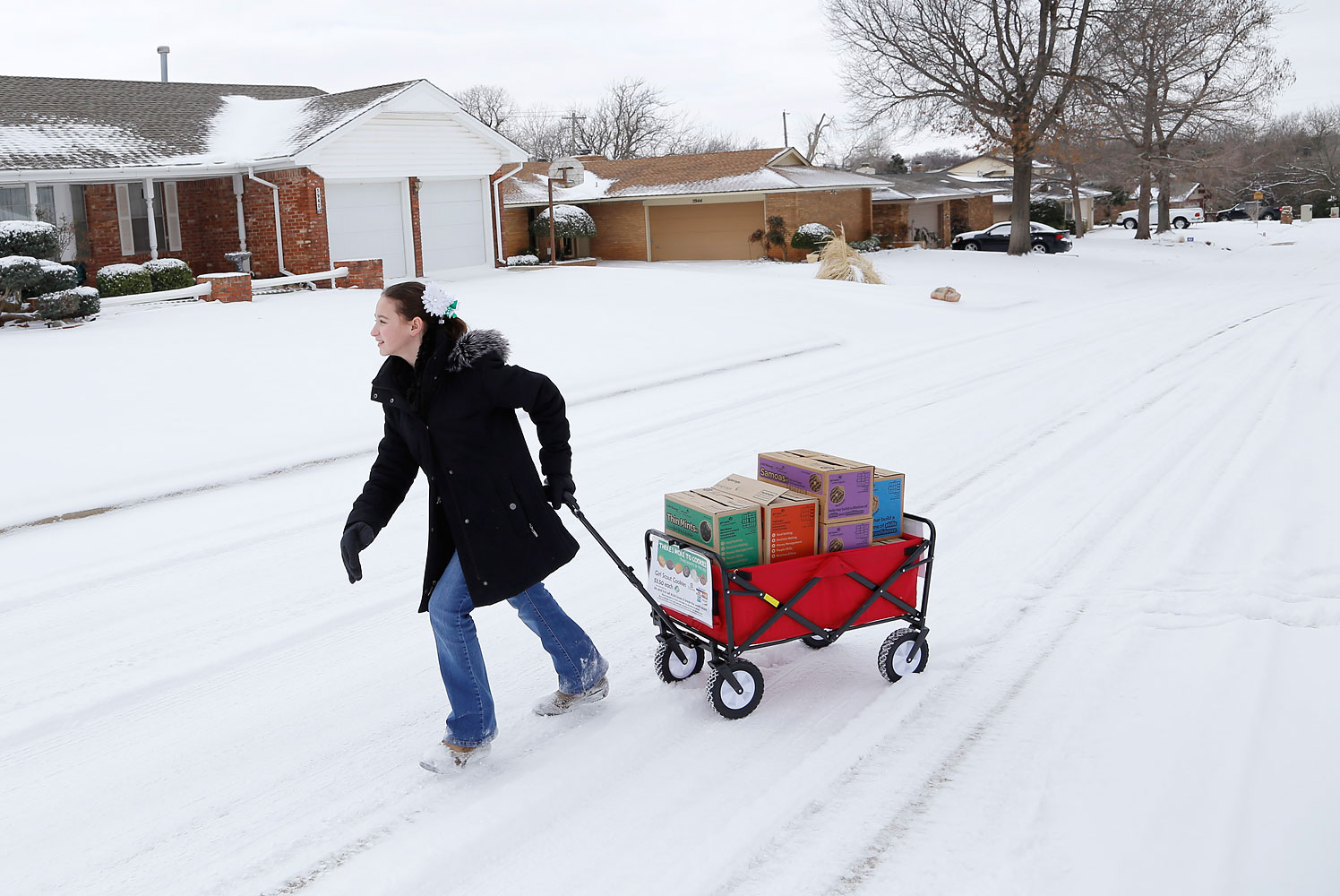 Girl Scout Katie Francis pulls her wagon full of boxes of cookies in the snow through a neighborhood in Warr Acres selling cookies in Oklahoma City, Feb. 6, 2014.