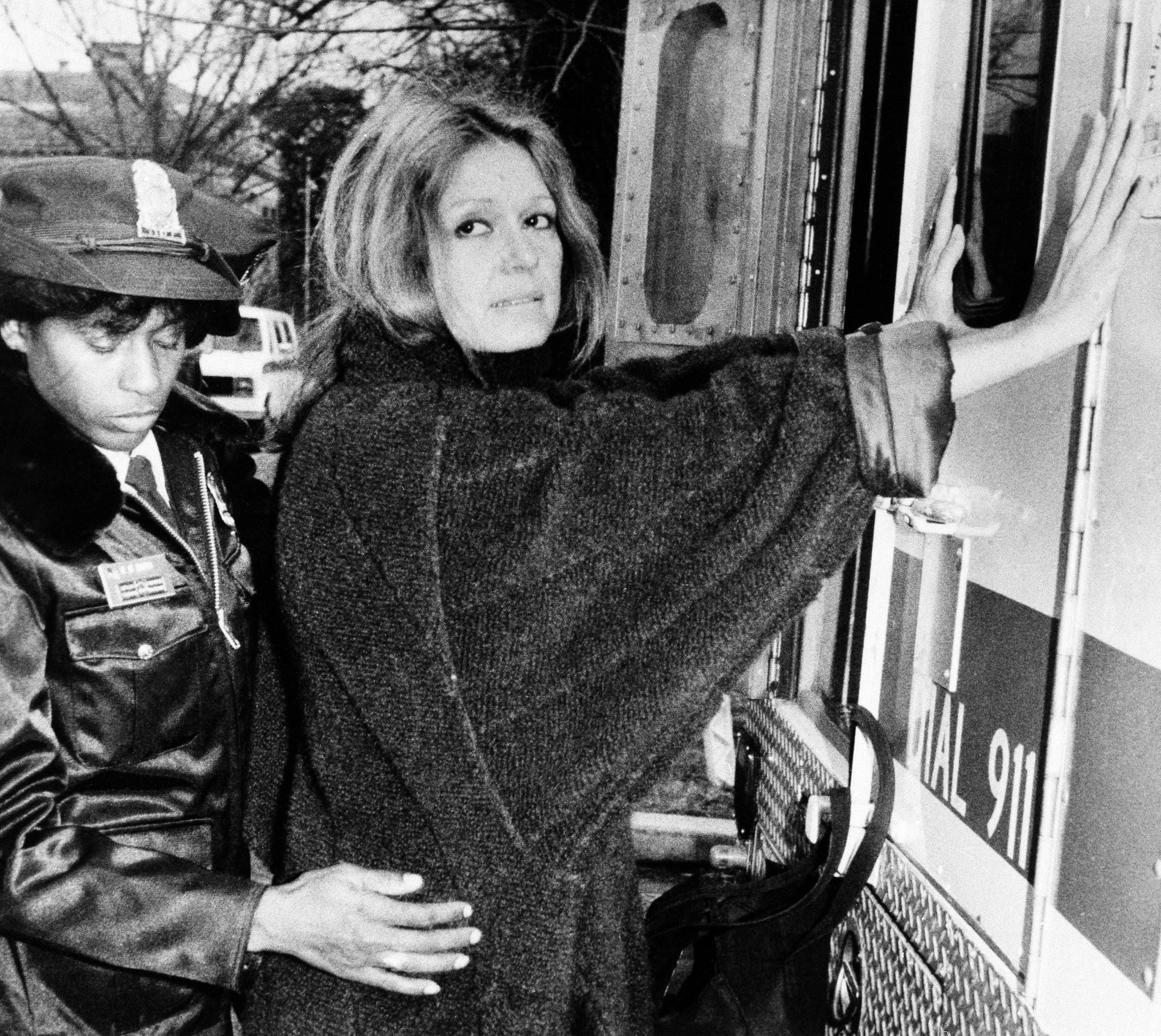 A uniformed officer arrests feminist Gloria Steinem during an anti-apartheid protest outside the South African Embassy in Washington, Dec. 19, 1984.