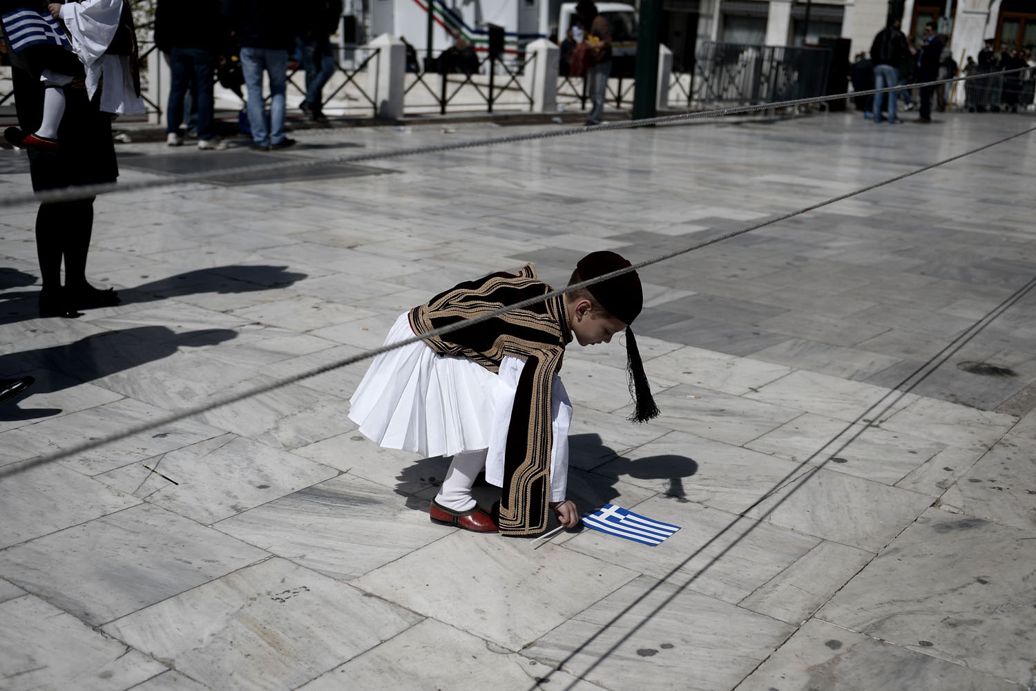 Mar. 25, 2014.                                A young boy picks up a Greek flag as he attends a military parade in central Athens during a ceremony marking the Greek Independence Day.
