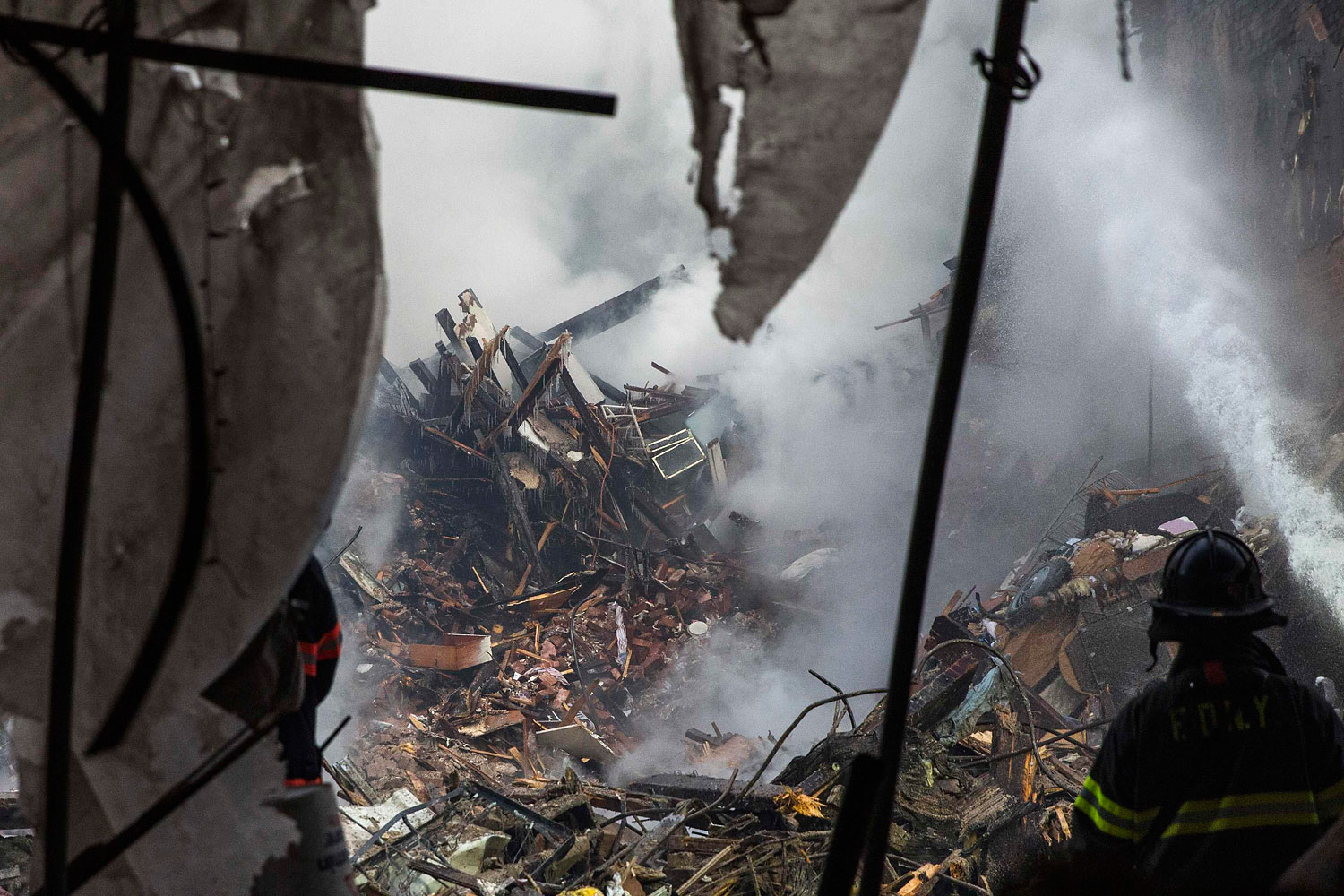 New York City emergency responders search through the rubble at the site of a building explosion in the Harlem section of New York, March 13, 2014.