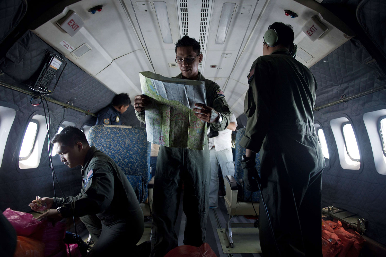 A Royal Malaysian Air Force Navigator captain, Izam Fareq Hassan, center, looks at a map onboard a Malaysian Air Force CN235 aircraft during a search and rescue (SAR) operation to find the missing Malaysia Airlines flight MH370 plane over the Strait of Malacca on March 14, 2014.