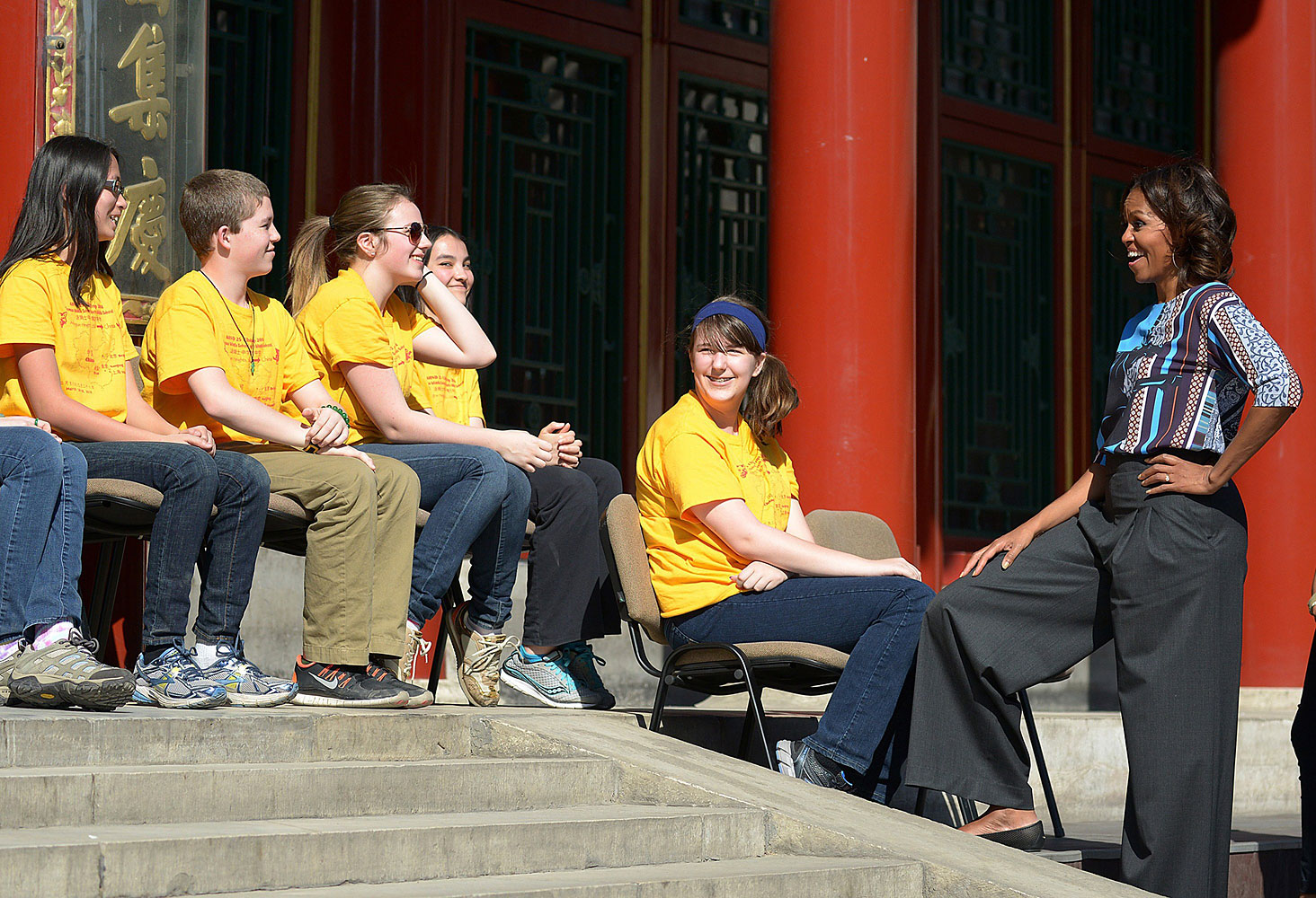 Wearing flared trousers and a patterned top, the First Lady speaks to a group of students from Chicago during her visit to the Summer Palace in Beijing on March 22, 2014.
