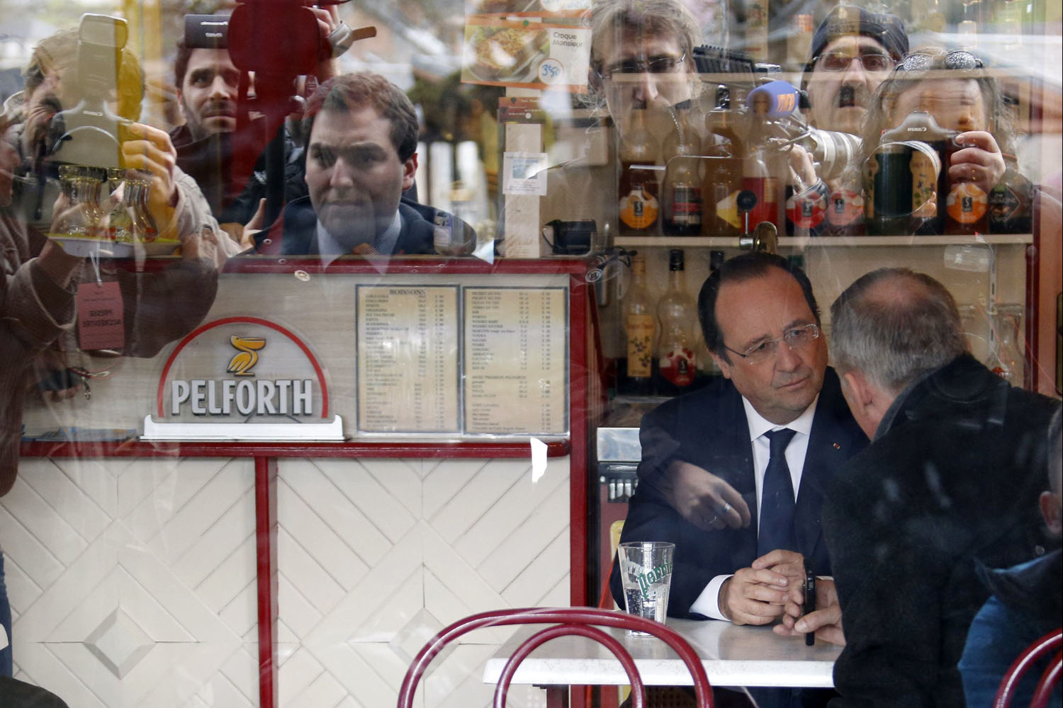 Mar. 23, 2014. French President Francois Hollande is seen speaking in a bar after voting in the first round in the French mayoral elections in Tulle.