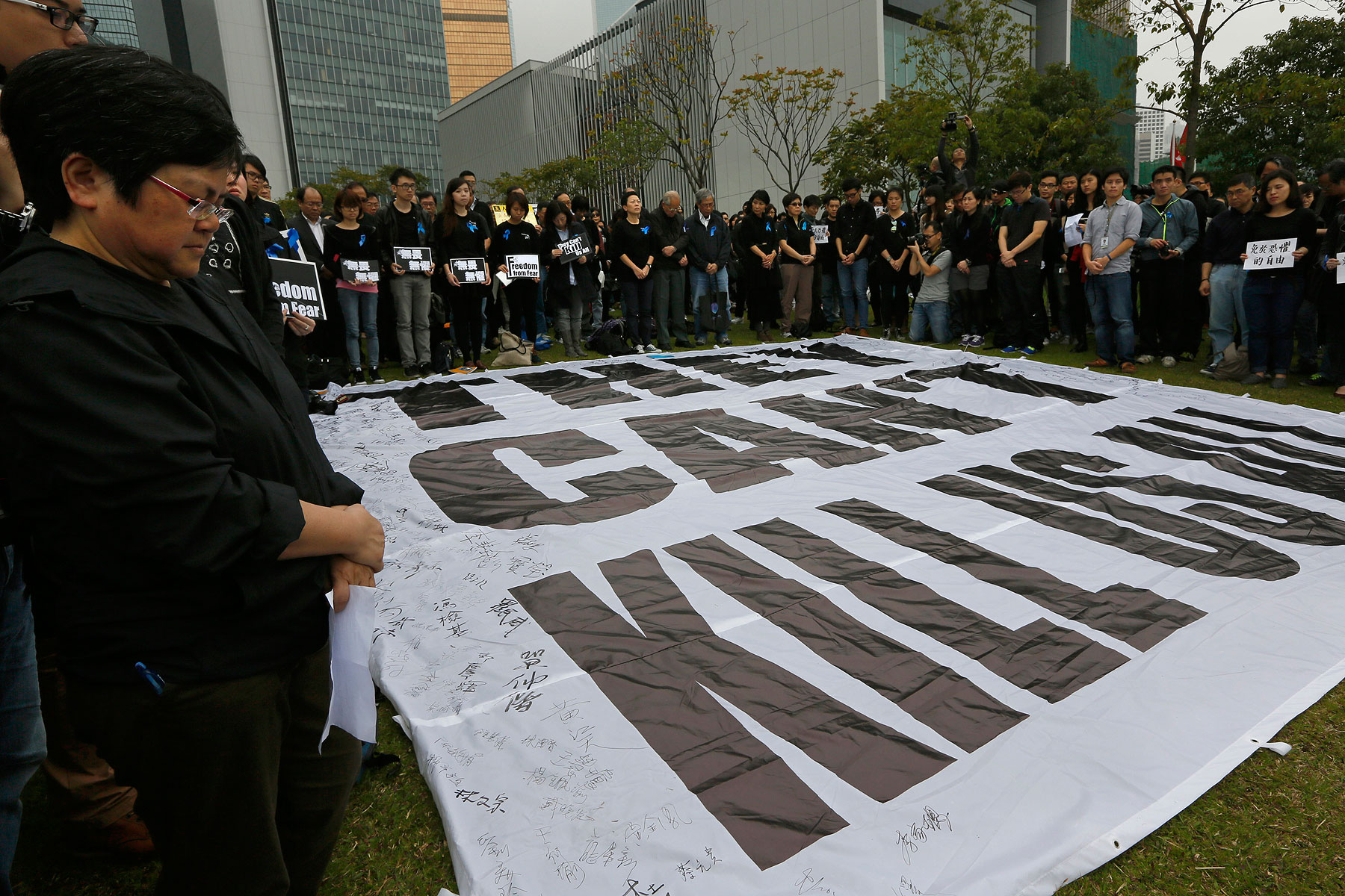 Journalists and their supporters stand in a five minutes silent around a huge banner reads   They can't kill us all   during a rally outside the government headquarter in Hong Kong, March 2, 2014