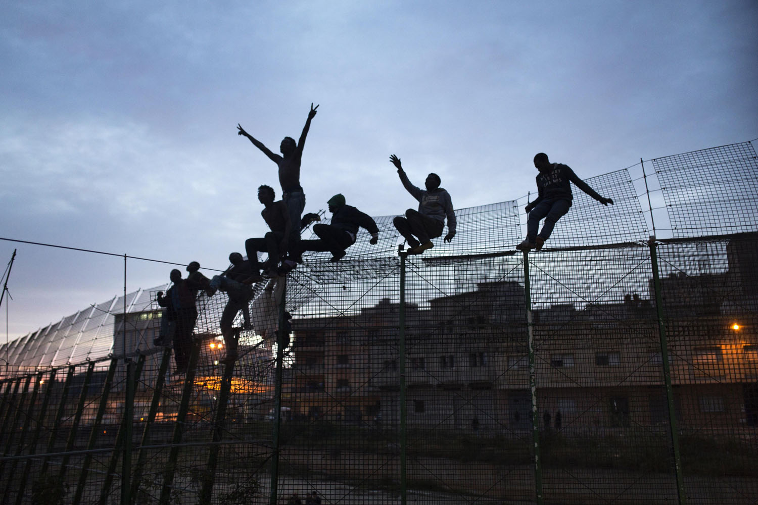 Mar. 28, 2014. Sub-Saharan migrants climb over a metallic fence that divides Morocco and the Spanish enclave of Melilla.