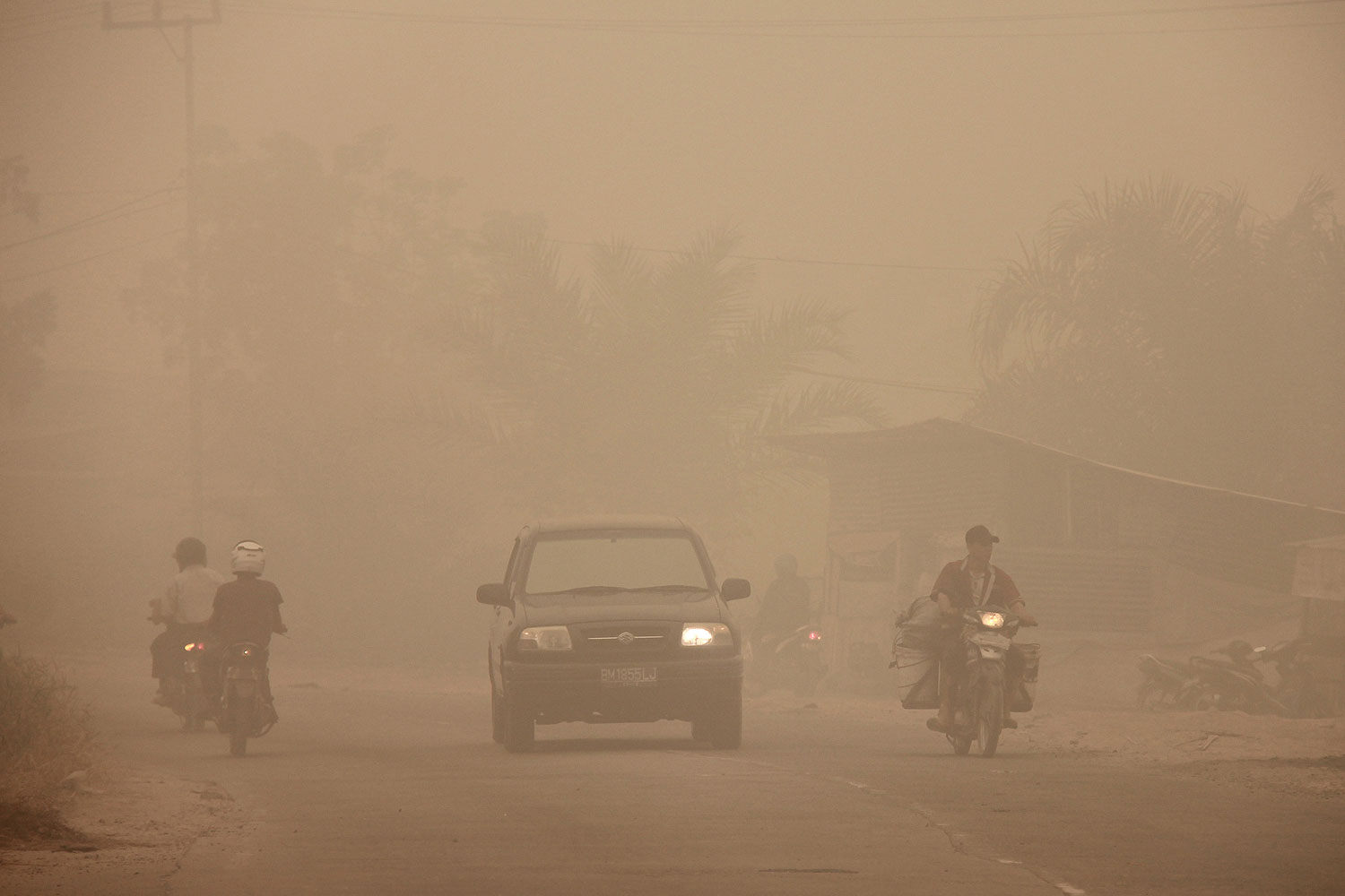 Indonesian motorists travel under a blanket of haze in Dumai town located in Riau province in Indonesia's Sumatra island on March 3, 2014. Riau province, the heart of a Southeast Asian smog crisis last year, has declared a state of emergency after being blanketed in thick haze from forest fires