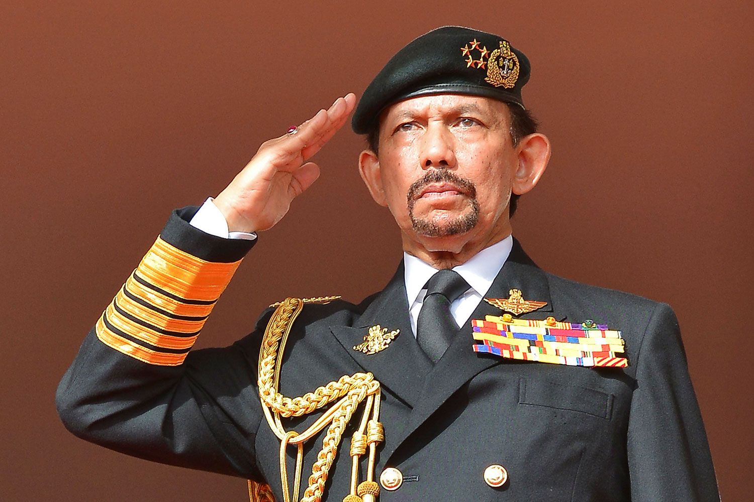 Brunei's Sultan Hassanal Bolkiah salutes as the national anthem is played during celebrations for Brunei's 30th National Day, in Bandar Seri Begawan on Feb. 23, 2014.
