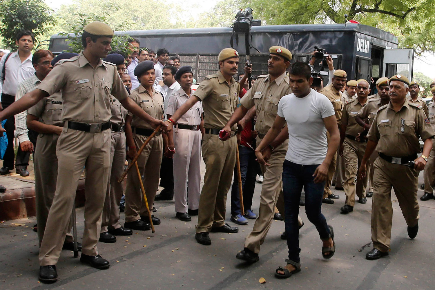 Vinay Sharma (wearing white T-shirt), one of the four men who were sentenced to death for fatally raping a young woman on a bus last December, is escorted by police outside a court in New Delhi Sept. 24, 2013.