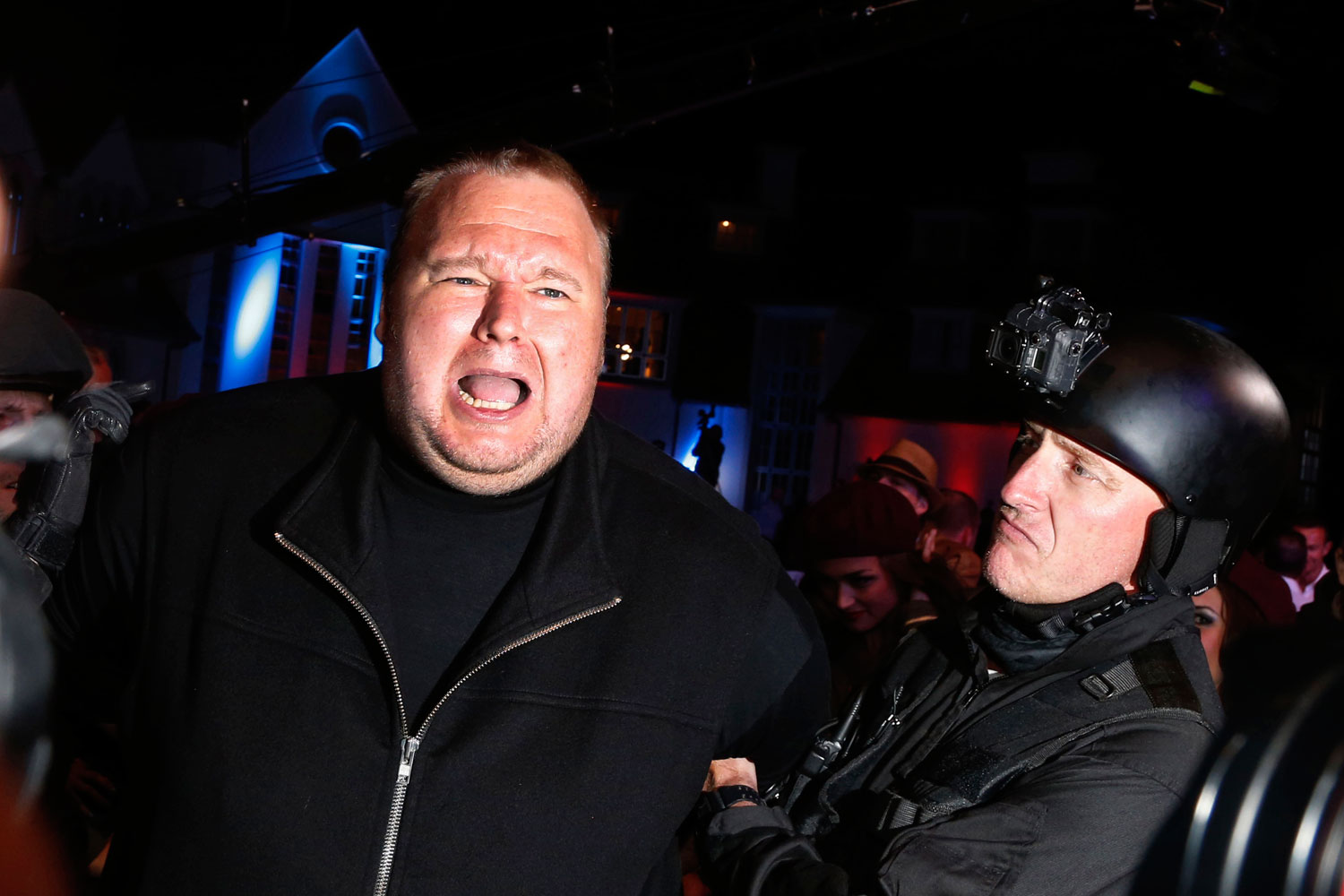 An actor in police costume mock-arrests Megaupload founder Kim Dotcom, left, as he launches his new file sharing site  Mega  in Auckland Jan. 20, 2013.