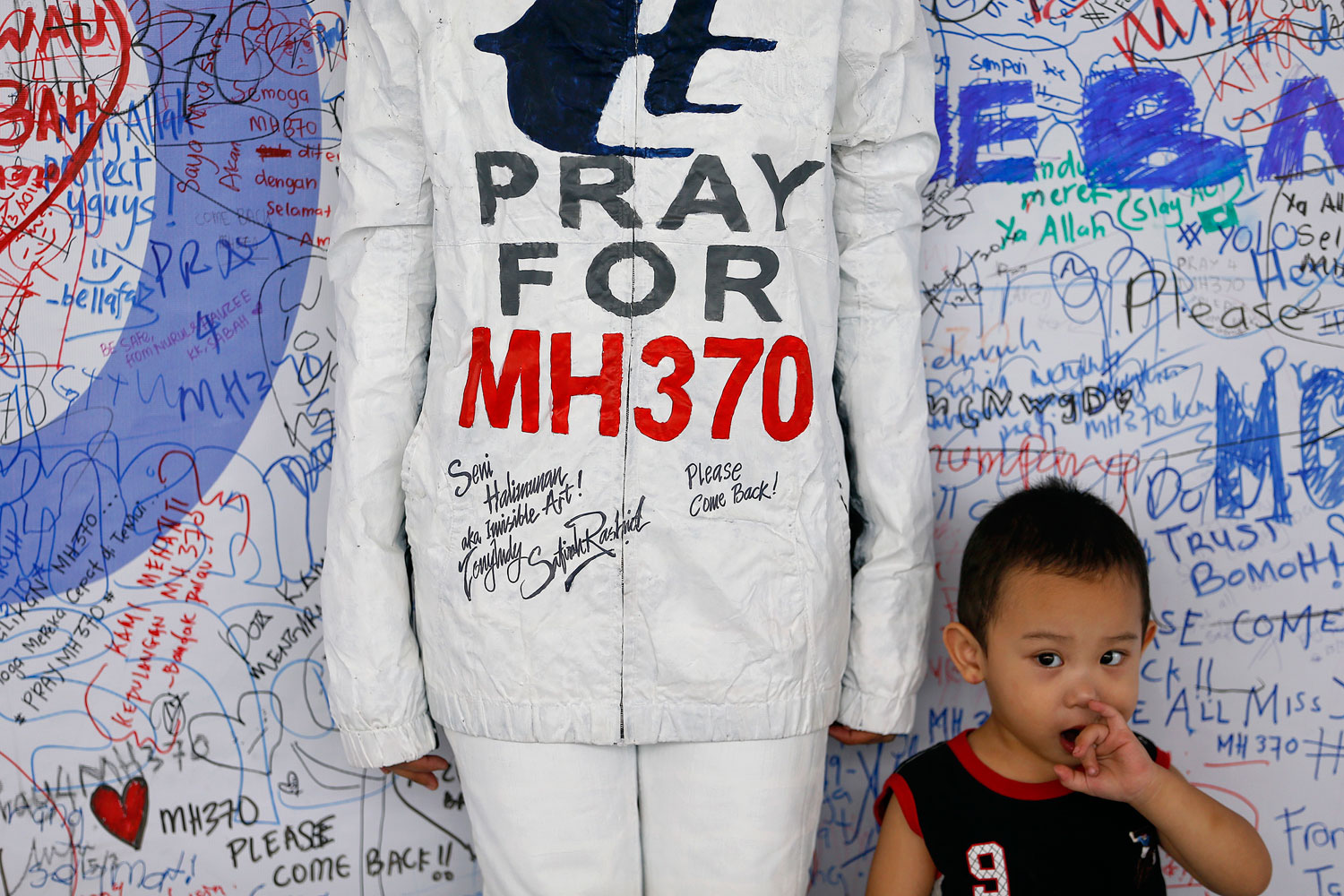 A boy stands beside a model posing for pictures during an art performance in support for the passengers of the missing Malaysia Airlines MH370 at the departure hall of the Kuala Lumpur International Airport March 17, 2014.