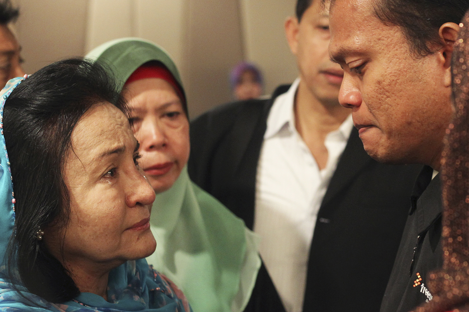 Rosmah Mansor, left, wife of Malaysian Prime Minister Najib Razak, cries with family members of passengers on the missing Malaysia Airlines flight MH370, at a hotel in Putrajaya March 9, 2014.