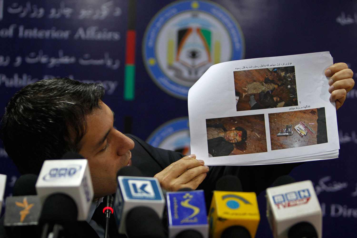 Afghanistan's interior ministry spokesman Sediq Sediqqi shows pictures of Taliban insurgents that were killed last night in a luxury hotel in Kabul March 21, 2014.