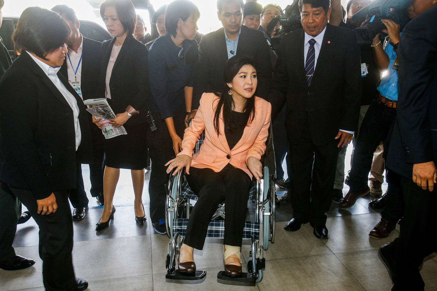 Thailand's Prime Minister Yingluck Shinawatra, center, arrives on a wheelchair at the Royal Police Cadet Academy in Nakorn Pathom province, March 18, 2014.