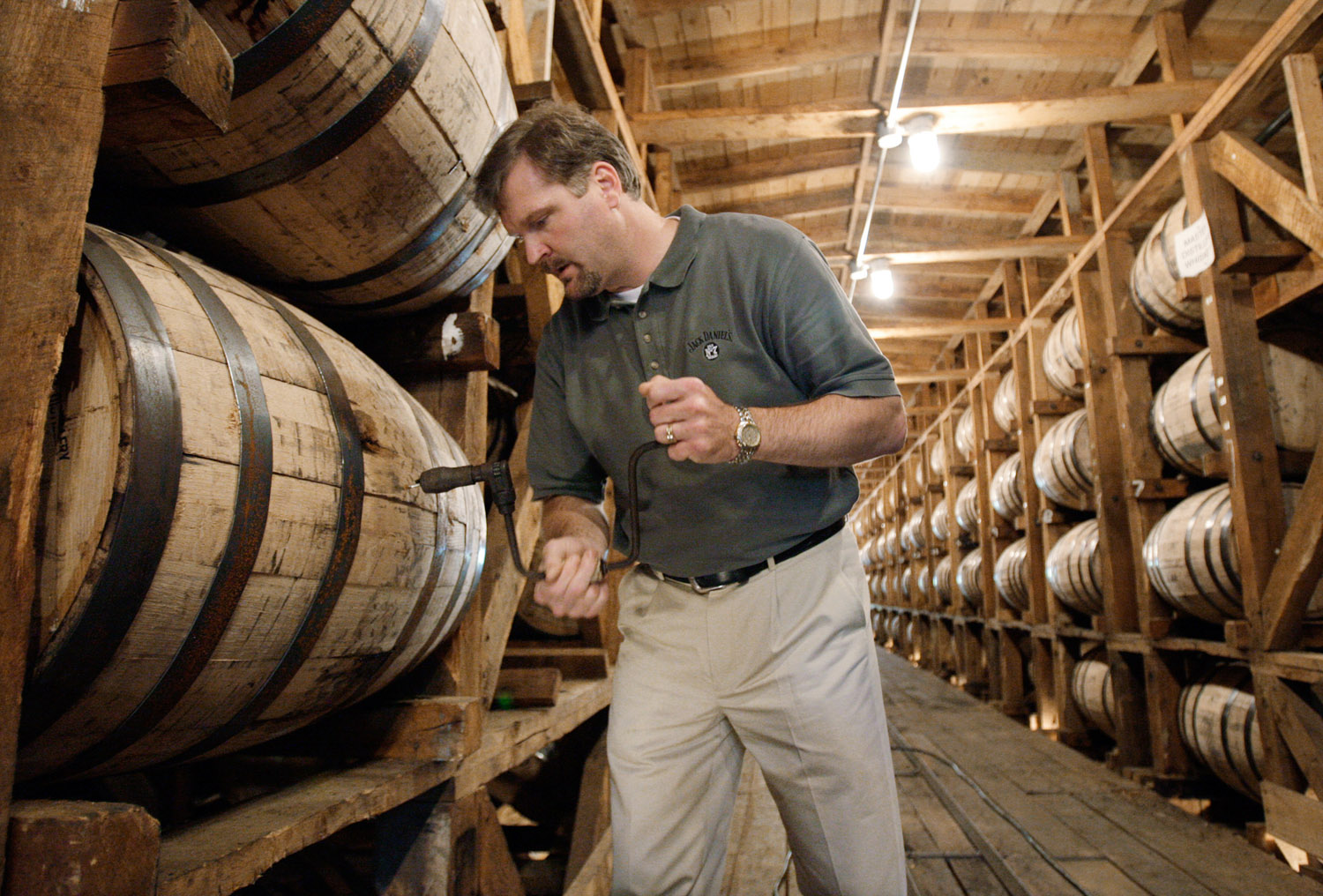 Jeff Arnett, the master distiller at the Jack Daniel Distillery in Lynchburg, Tenn., drills a hole in a barrel of whiskey in one of the aging houses at the distillery, May 20, 2009.