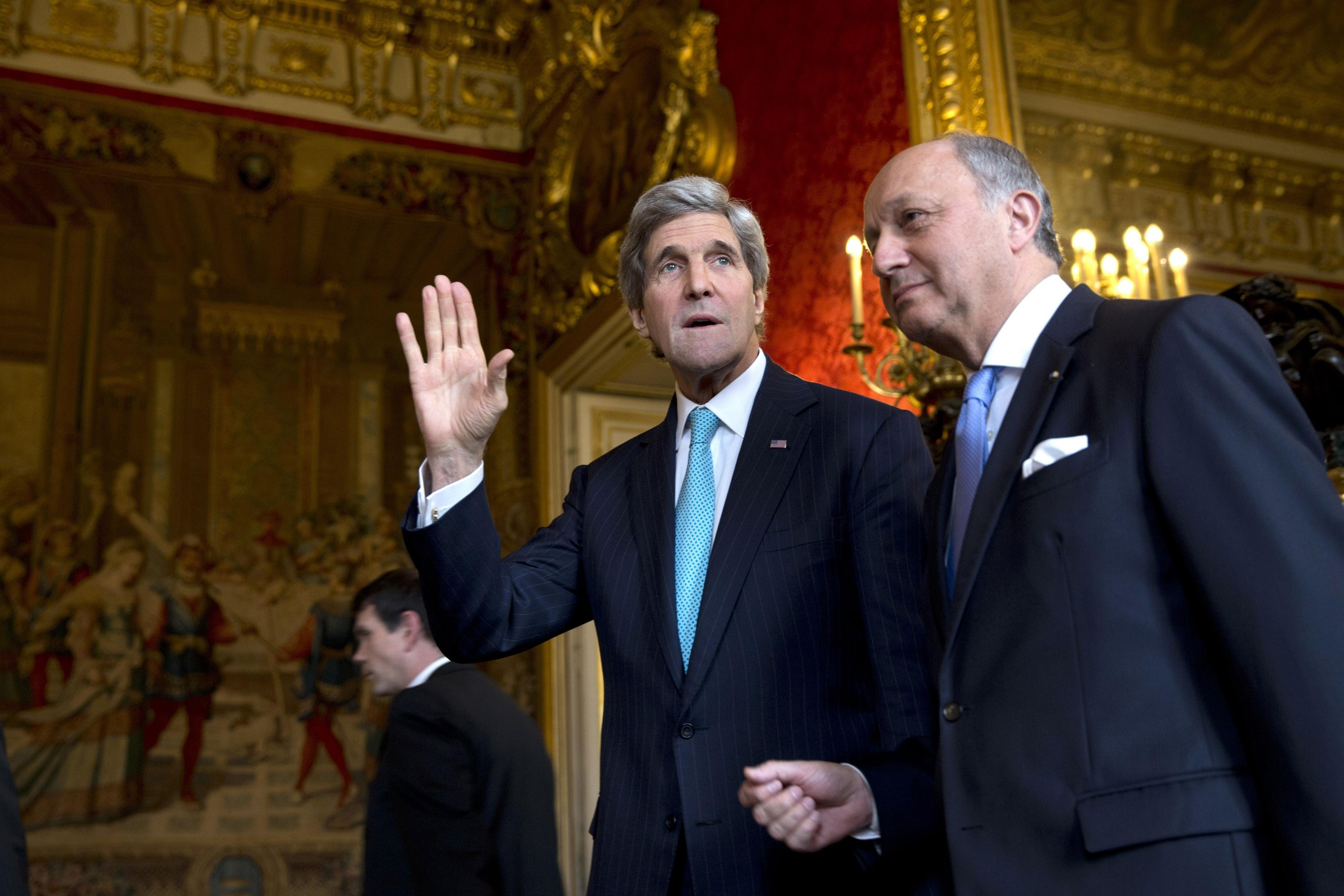 From left: U.S. Secretary of State John Kerry waves to the waiting media as he walks with French Foreign Minister Laurent Fabius for their meeting at the Quai d'Orsay in Paris, on March 30, 2014.