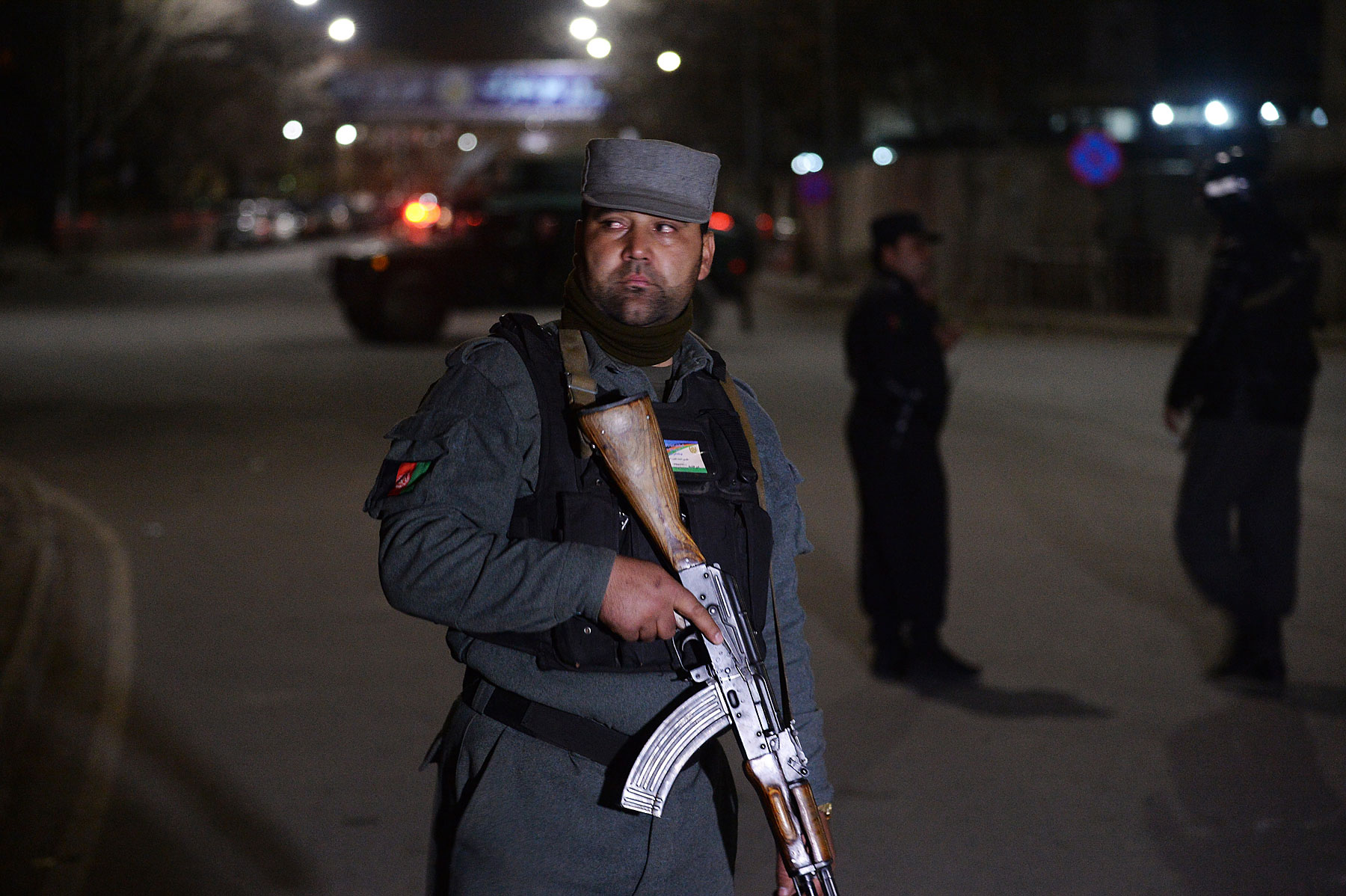 An Afghan policeman stands guard near the security perimeter setup around the Serena hotel in Kabul late on March 21, 2014.