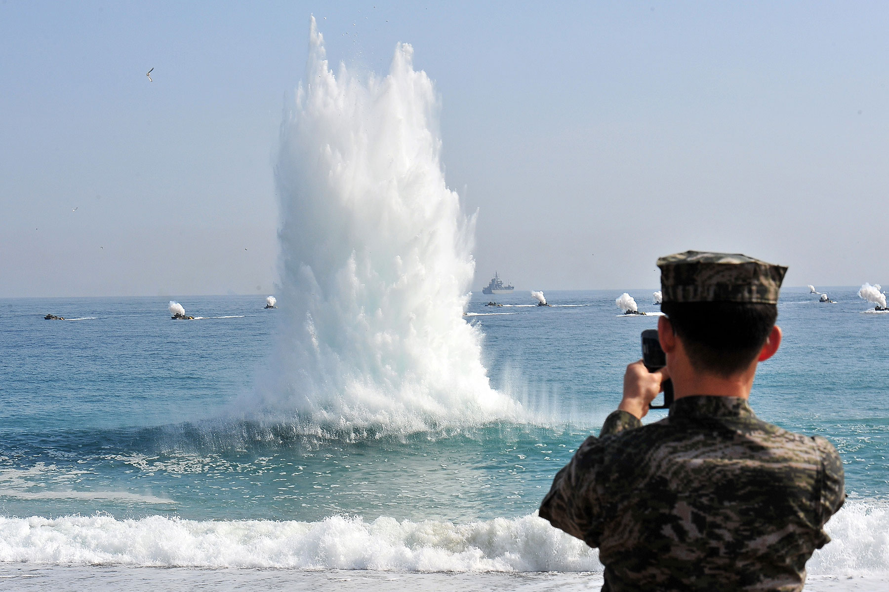 A South Korean Marine stands on a beach as amphibious assault vehicles (in background) approach the seashore during a joint landing operation by US and South Korean Marines in Pohang, 270 kms southeast of Seoul, on March 31, 2014