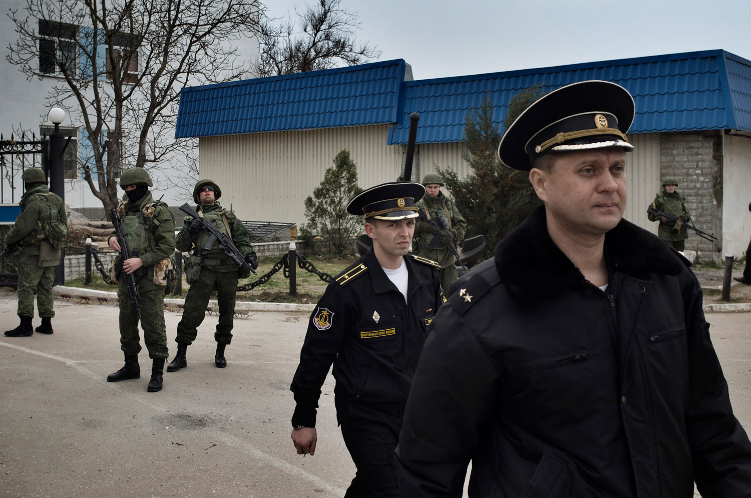 Ukrainian naval officers passed by Russian military personnel as they left the Ukrainian naval headquarters in Sevastopol on Wednesday after Russian forces and local militiamen seized control of the facility, March 19, 2014.
