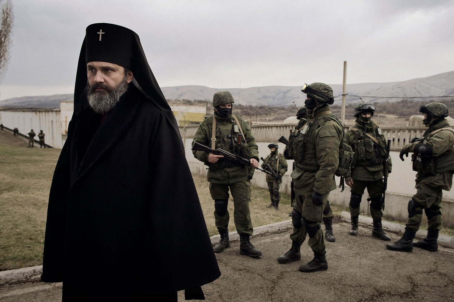 A priest stands next to troops in Perevalnoye on Sunday.