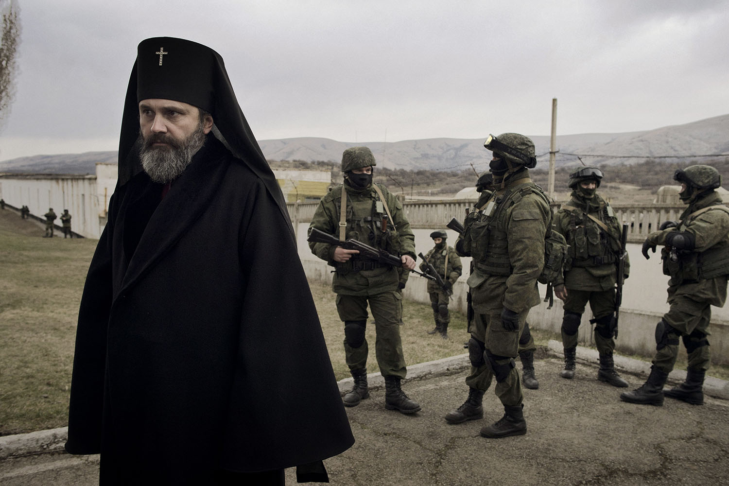 Mar. 2, 2014. Archbishop Kliment of Crimea stands next to Russian soldiers, who are not wearing any identifying markers on their uniforms, outside the blocked Ukrainian military base  in the village of Perevalnoye. The Archbishop came to support Ukrainians and acted as a human shield                       from a possible Russian attack.