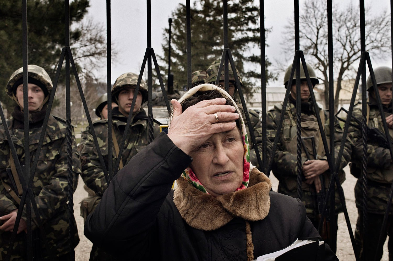 A Ukrainian woman reacts as troops in unmarked uniforms hold positions in Perevalnoye, a small Ukrainian base roughly 15 miles south of Simferopol on Sunday, March 2, 2014. About two dozen Ukrainian soldiers could be seen behind her.