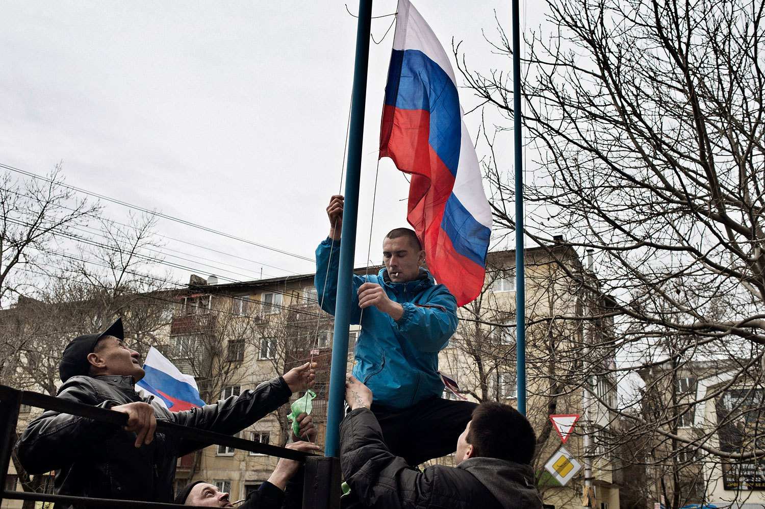 Members of a pro- Russian group raise a Russian flag in front of a military base in Simferopol on Sunday.