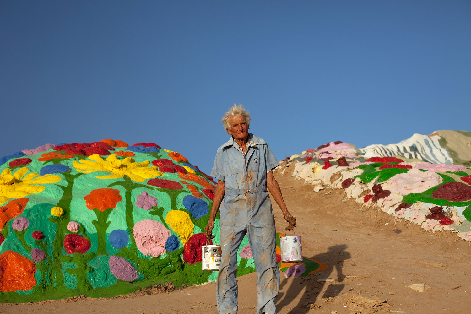 Knight paints a peripheral mound covered in flowers, one of his common themes.