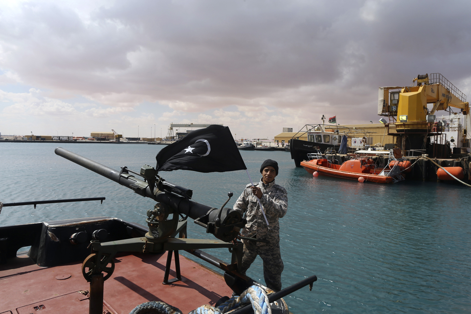 A rebel under Ibrahim Jathran holds the Cyrenaica flag while standing on a boat at Es Sider port in Ras Lanuf, where a North Korean-flagged tanker had loaded crude oil, March 11, 2014.