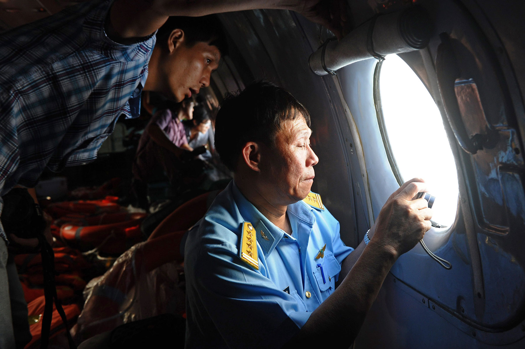 A Vietnamese Air Force officer, right, and a reporter look out the window during search operations over the southern seas off Vietnam on March 9, 2014.