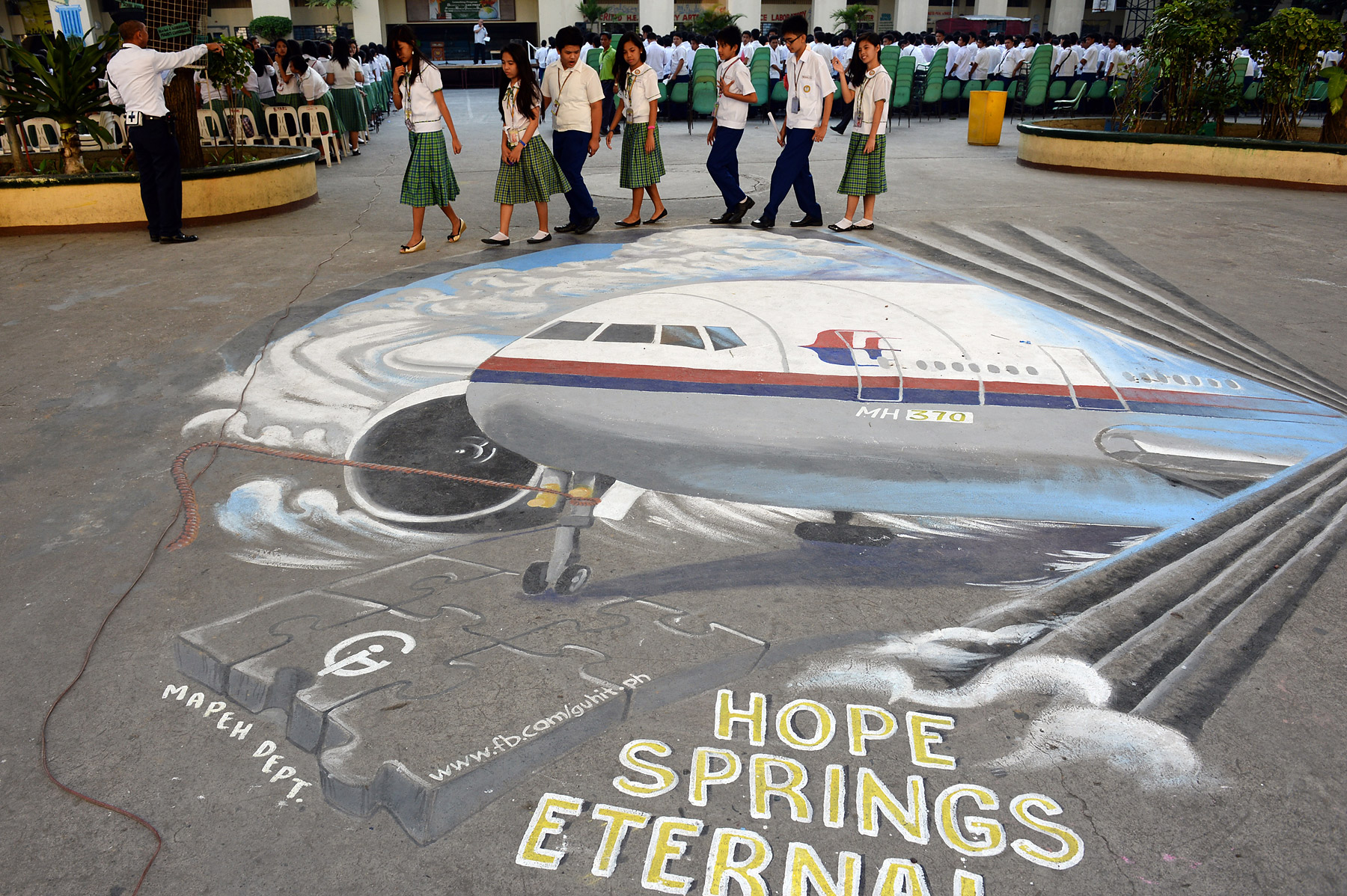Students walk past a giant mural featuring the missing Malaysia Airlines Flight MH370, on the grounds of their school in Manila's financial district of Makati on March 18, 2014