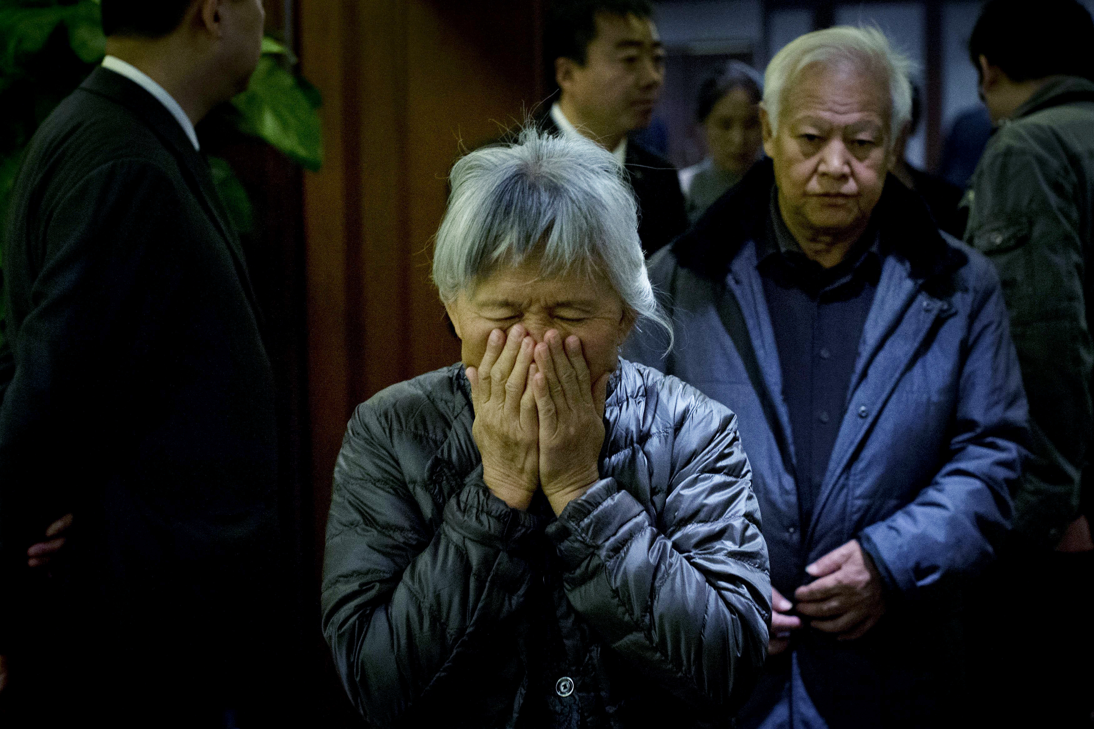 An elderly woman, one of the relatives of Chinese passengers aboard missing Malaysia Airlines Flight MH370, covers her face out of frustration as she leaves a hotel ballroom after a daily briefing meeting with managers of Malaysia Airlines in Beijing, on March 19, 2014.