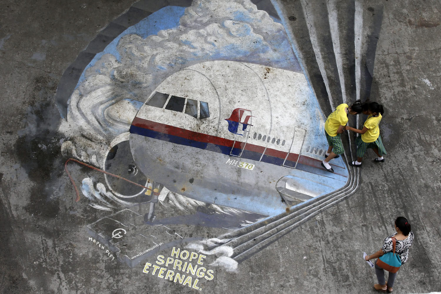 Mar. 25, 2014. Pupils of Benigno Ninoy Aquino High School stand on a painting of Malaysia Airlines Flight MH370 at the school grounds in Makati City, south of Manila, Philippines, Filipino artists painted the image to express hope and solidarity for the passengers and crew of the missing flight.