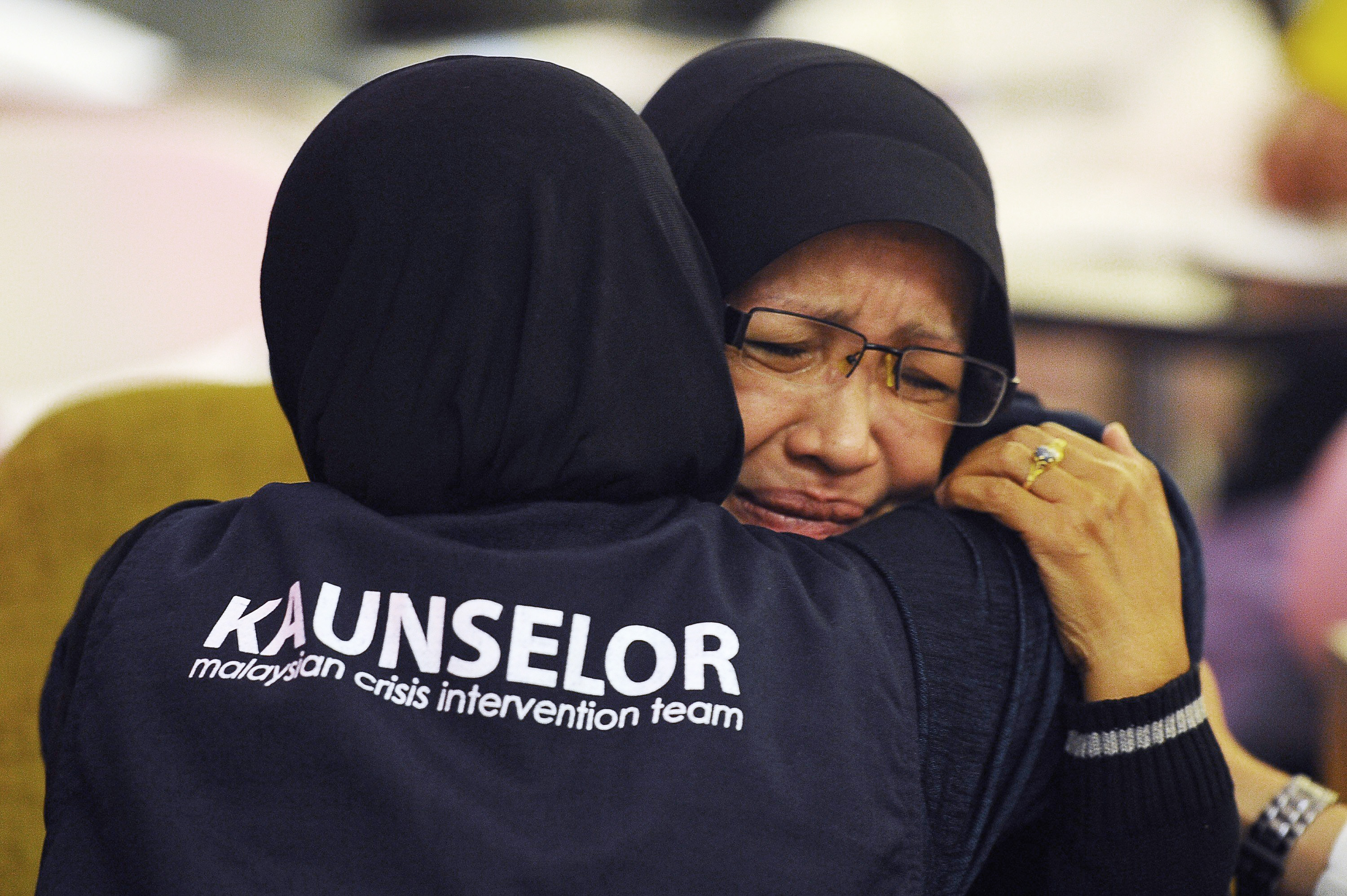 A family member of one of the passengers aboard a missing plane is consoled by a crisis counselor at a hotel in Putrjaya, outside Kuala Lumpur, on March 9, 2014.