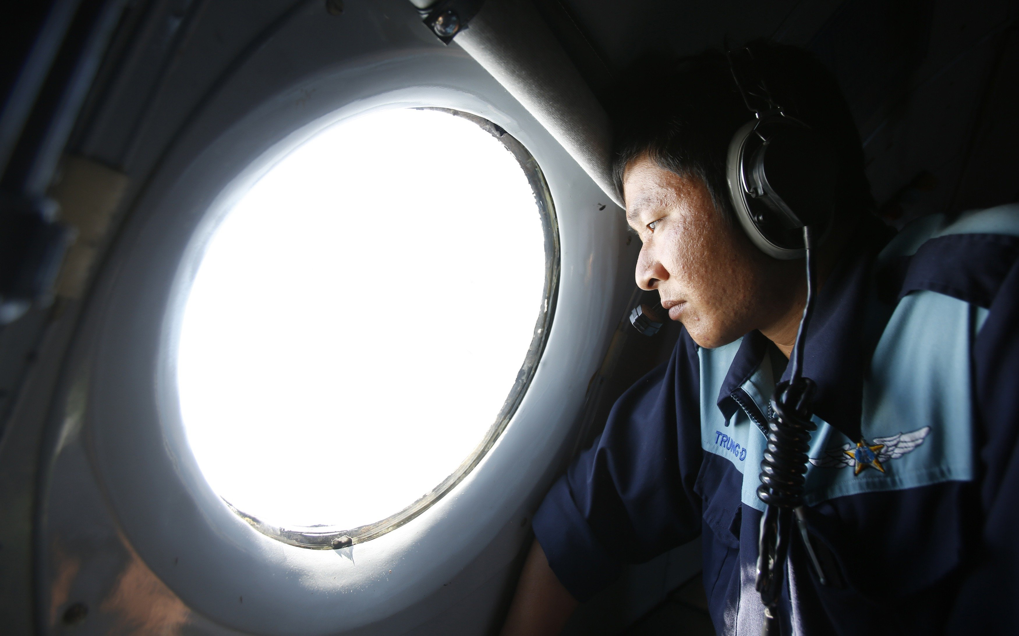 Military officer Nguyen Tran looks out from a Vietnam Air Force AN-26 aircraft during a mission to find the missing Malaysia Airlines flight MH370, off Con Dao island, on March 14, 2014.