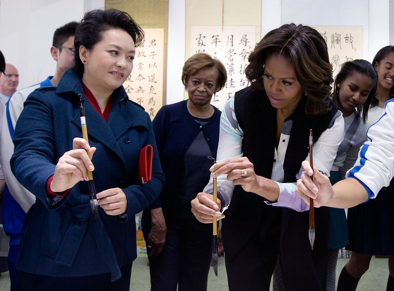 Peng Liyuan, wife of Chinese President Xi Jinping shows U.S. first lady Michelle Obama how to hold a writing brush as they visit a Chinese traditional calligraphy class at the Beijing Normal School, a school that prepares students to go abroad in Beijing, March 21, 2014.