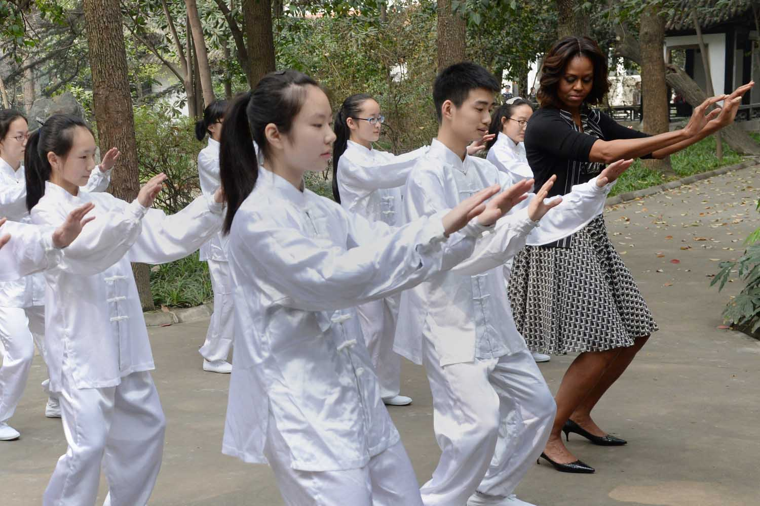 Mar. 25, 2014. US First Lady Michelle Obama (R) performs Tai Chi with students from the Chengdu No.7 High School in China's southwest Sichuan province.