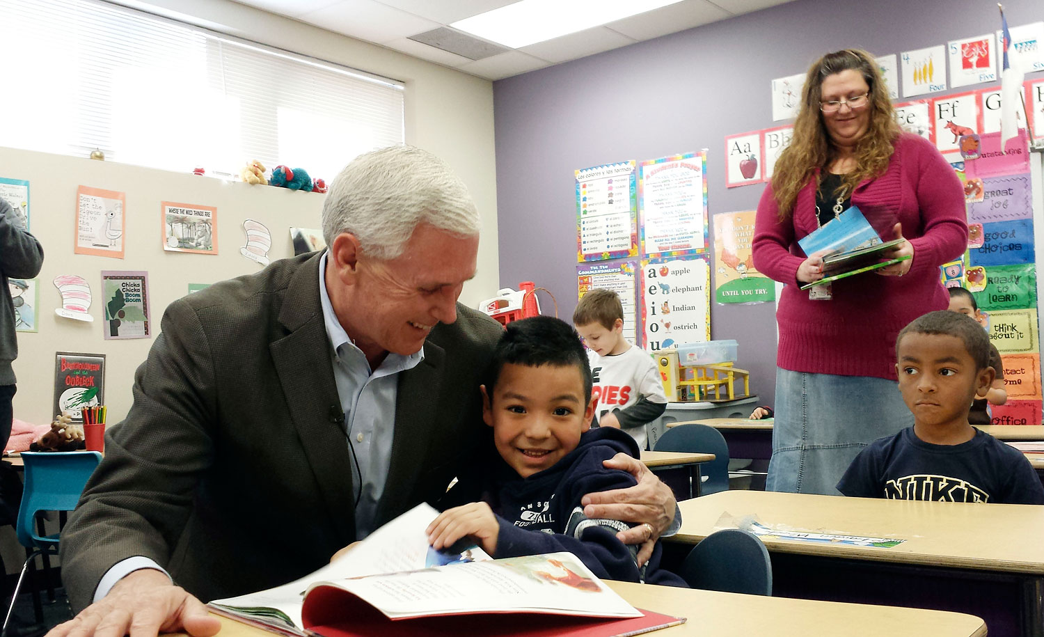 Indiana Republican Gov. Mike Pence embraces a preschool student at the Shepherd Community Center in Indianapolis, Feb. 26, 2014.