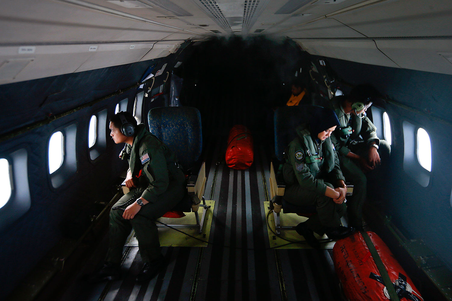 Crew members from the Royal Malaysian Air Force look through windows of an aircraft during an operation to find Malaysia Airlines Flight 370 in the Strait of Malacca on March 13, 2014