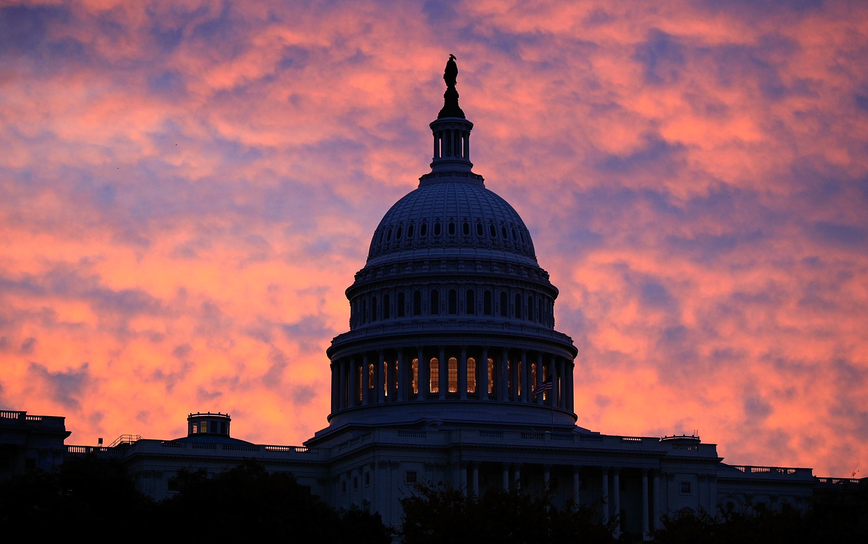 The early morning sun rises behind the US Capitol Building in Washington, DC.